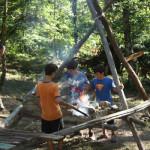 ragazzi in campeggio che cucinano alla trapper
