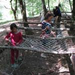 ragazzi in campeggio che costruiscono strutture in legno ed eseguono nodi e legature